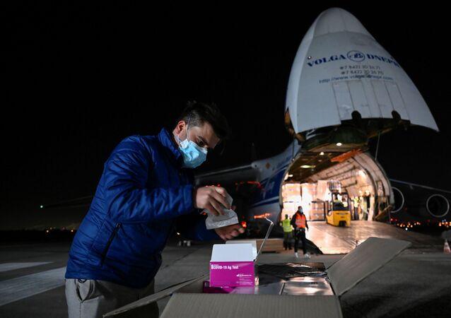 Muž otevírá test antigenu pro pilotní fázi hromadného testování na covid-19 na bratislavském letišti