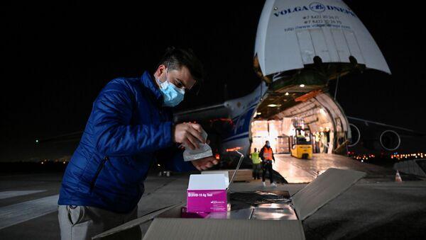 Muž otevírá test antigenu pro pilotní fázi hromadného testování na covid-19 na bratislavském letišti - Sputnik Česká republika
