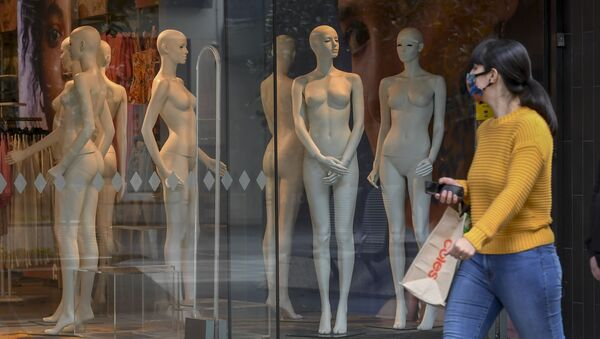 Žena v ochranné masce prochází kolem výlohy v Melbourne, Austrálie - Sputnik Česká republika