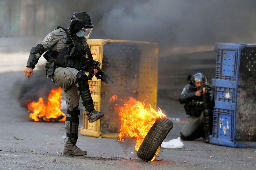 Důstojník izraelské policie kope do hořící pneumatiky během protiizraelské protestní akce v Hebronu na Západním břehu Jordánu