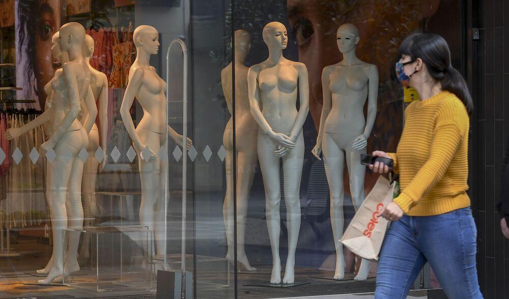 Žena v ochranné masce prochází kolem výlohy v Melbourne, Austrálie