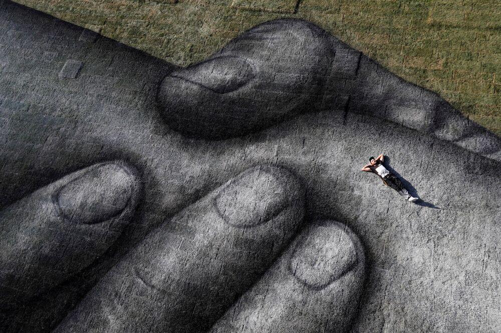Umělec Saype pózuje při práci na svém díle v Istanbulu v Turecku