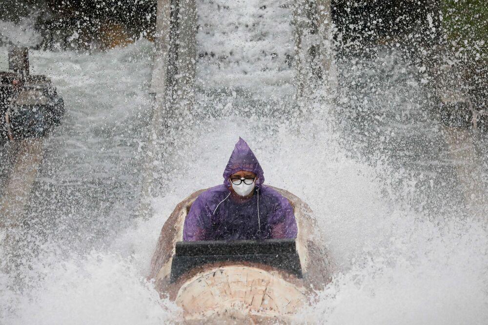 Muž v ochranné masce se baví v zábavním parku v Santa Rose, Filipíny