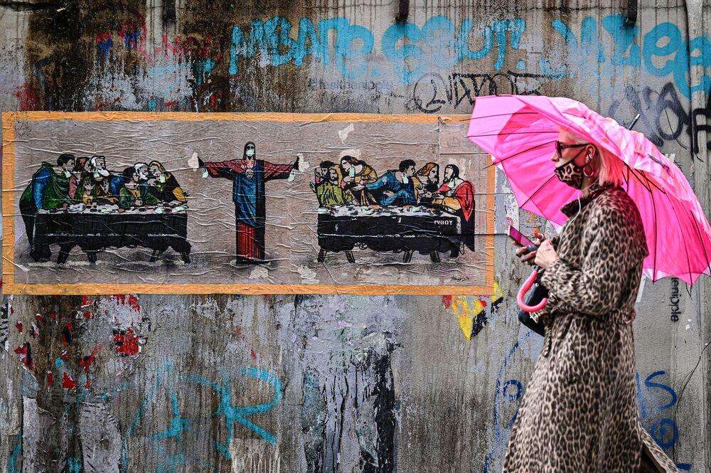 Žena v leopardí ochranné masce na pozadí graffiti italského umělce TvBoy v Miláně, Itálie