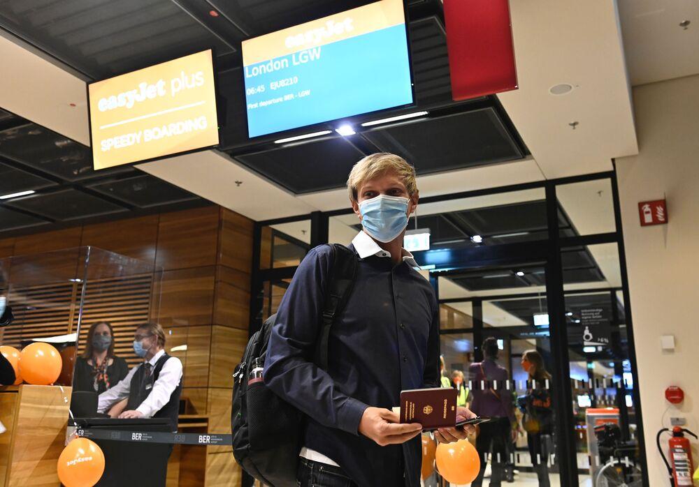 Cestující v lékařské masce na novém mezinárodním letišti Willyho Brandta v Německu