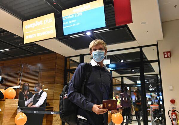 Cestující v lékařské masce na novém mezinárodním letišti Willyho Brandta v Německu - Sputnik Česká republika