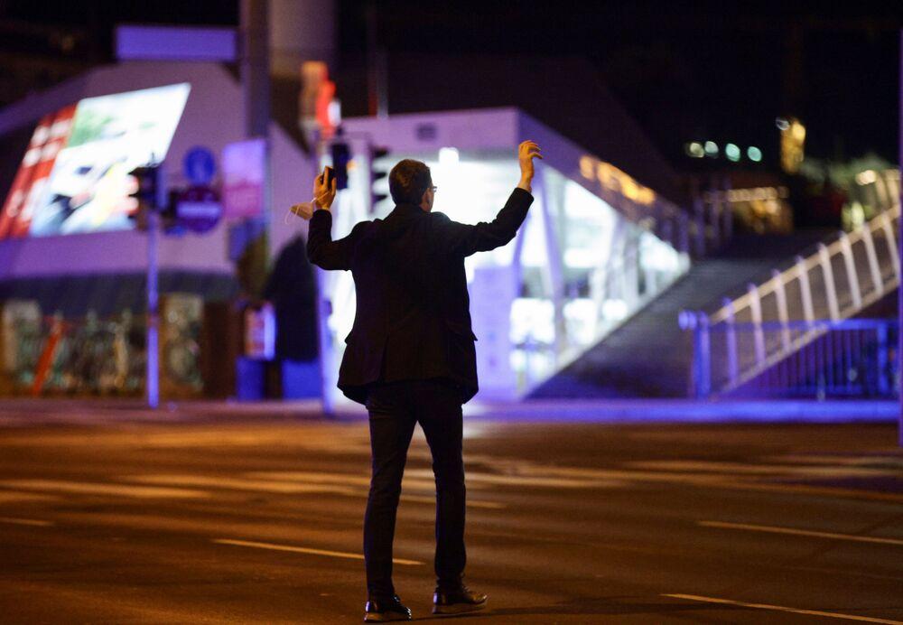 Muž drží ruce nad hlavou při policejní kontrole po střelbě útočníků, Rakousko 2. listopadu 2020