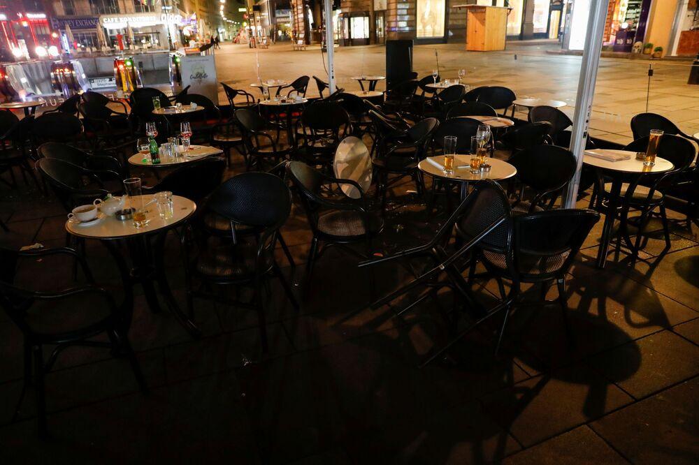 Neuklizené jídelní příbory a sklenice v kavárně po střelbě ve Vídni