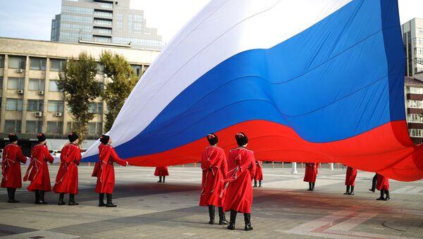 Slavnostní ceremoniál vztyčení státní vlajky Ruské federace kozáky čestné stráže kubánského kozáckého vojska v Den národní jednoty na hlavním náměstí ve městě Krasnodar - Sputnik Česká republika