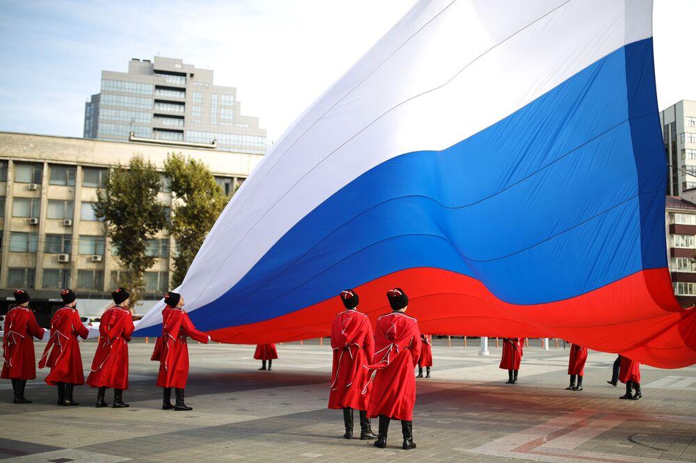 Slavnostní ceremoniál vztyčení státní vlajky Ruské federace kozáky čestné stráže kubánského kozáckého vojska v Den národní jednoty na hlavním náměstí ve městě Krasnodar