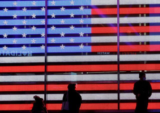 Lidé u elektronické vlajky USA na Times Square