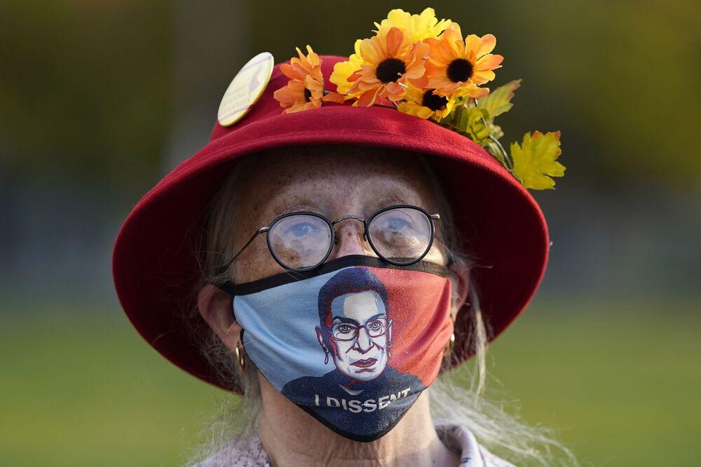 Žena v roušce s portrétem soudkyně Nejvyššího soudu Ruth Baderové Ginsburgové během protestu v Portlandu.