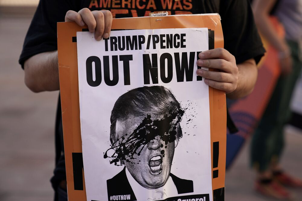 Protestující z města Los Angeles drží ceduli zobrazující prezidenta Donalda Trumpa.