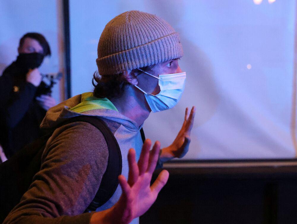 Demonstrant zvedá ruce před policií a dává najevo, že se vzdává. Protest v Portlandu následující den po volbách.