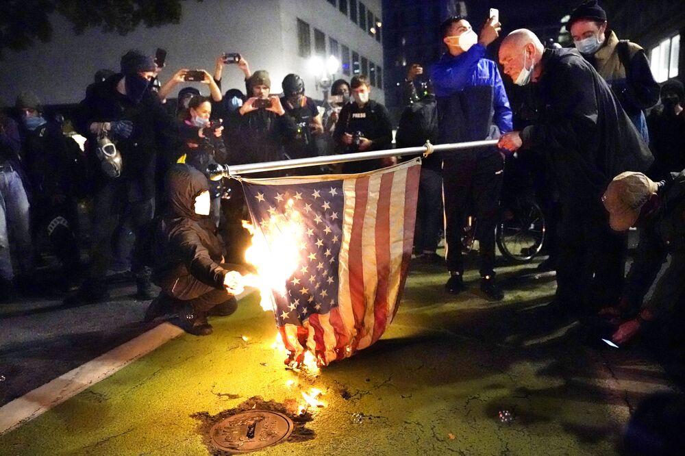 Protestující zapaluje americkou vlajku během demonstrace v Portlandu.