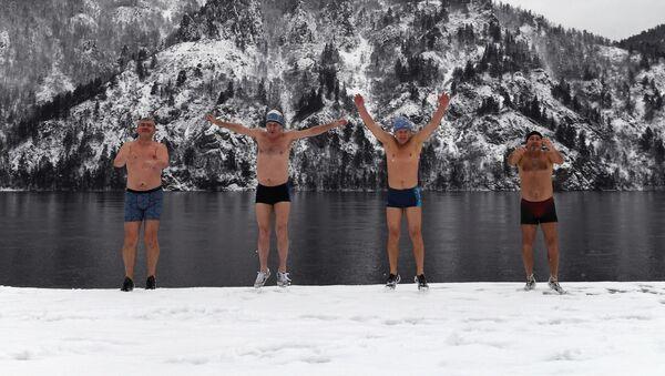 Členové zimního plaveckého klubu Delfín se zahřívají na nábřeží před koupáním v řece Jenisej v Divnogorsku  - Sputnik Česká republika