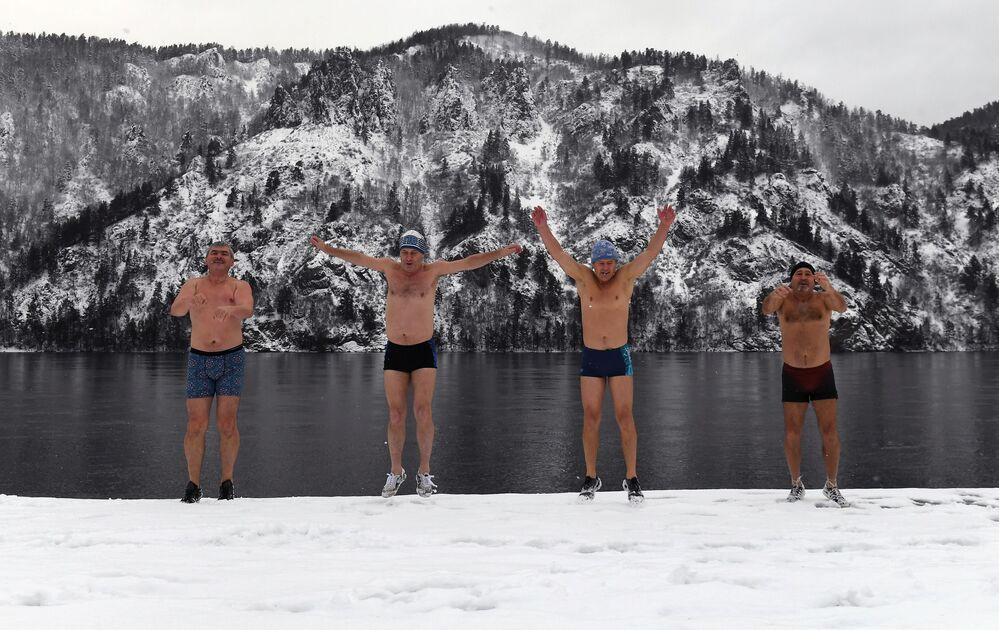 Členové zimního plaveckého klubu Delfín se zahřívají na nábřeží před koupáním v řece Jenisej v Divnogorsku