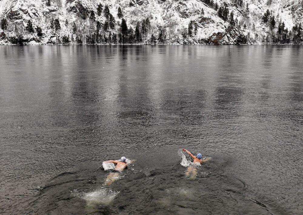 Členové zimního plaveckého klubu Delfín plavou v ledové řece Jenisej v Divnogorsku