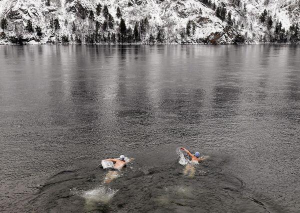 Členové zimního plaveckého klubu Delfín plavou v ledové řece Jenisej v Divnogorsku - Sputnik Česká republika