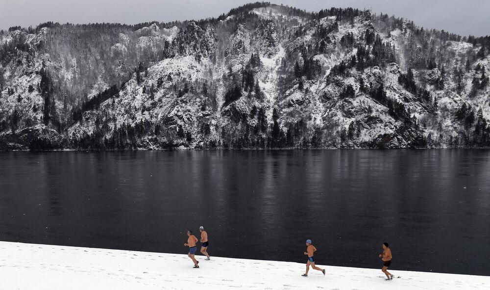 Členové zimního plaveckého klubu Delfín pobíhají po nábřeží před koupáním v řece Jenisej v Divnogorsku