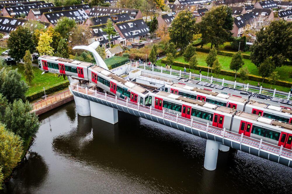 Foto z města Spijkenisse v Nizozemsku. Vlak metra prorazil bezpečnostní bariéru a uvízl na soše velrybího ocasu.