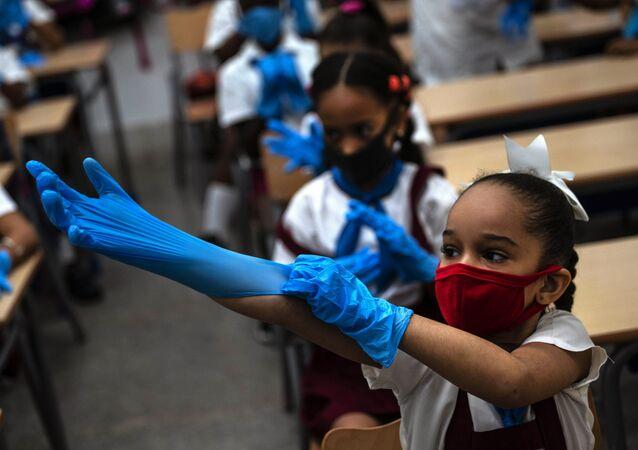 Žáci v ochranných rukavicích a rouškách ve škole, Havana