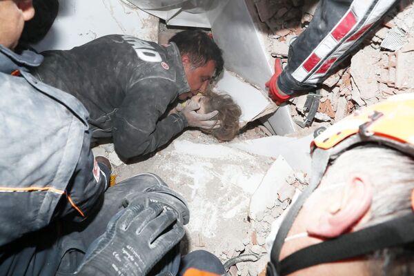 Záchranáři vytahují dítě zpod trosek po zemětřesení v tureckém Izmiru. - Sputnik Česká republika