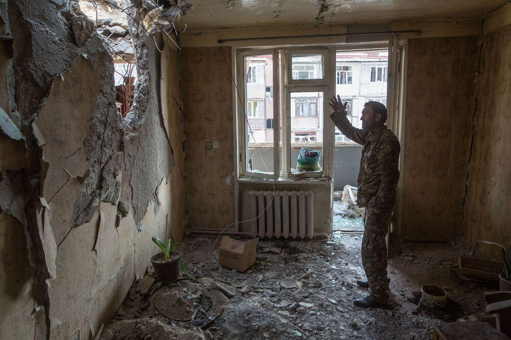 Muž ve zničeném bytě ve Stěpanakertu, Náhorní Karabach.