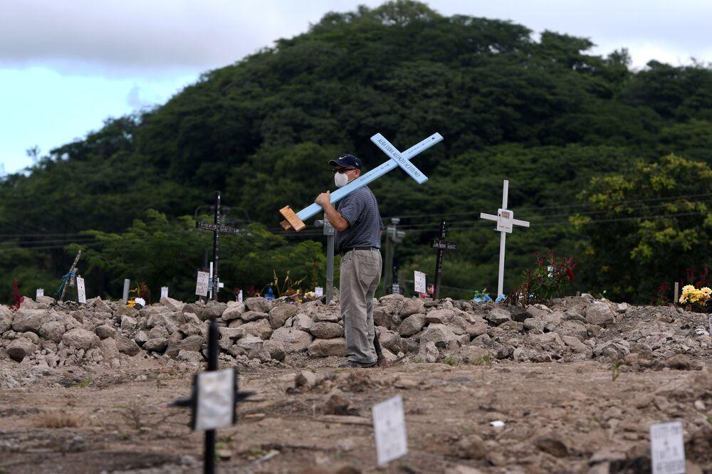 Muž s křížem na hřbitově během Dne mrtvých v Hondurasu.