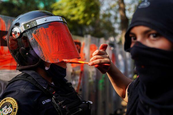 Dívka maluje helmu policisty během protestu proti násilí vůči ženám a policejnímu násilí v Mexico City - Sputnik Česká republika