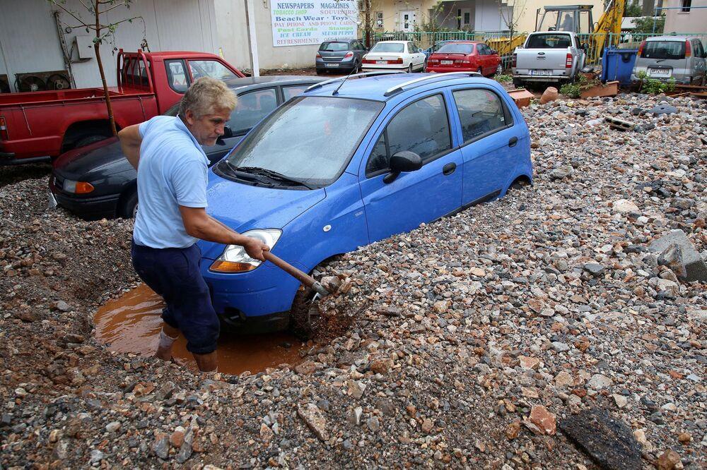 Muž vykopává své auto po silných deštích v místě Malia na ostrově Kréta, Řecko