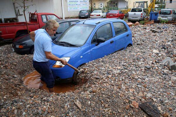 Muž vykopává své auto po silných deštích v místě Malia na ostrově Kréta, Řecko - Sputnik Česká republika