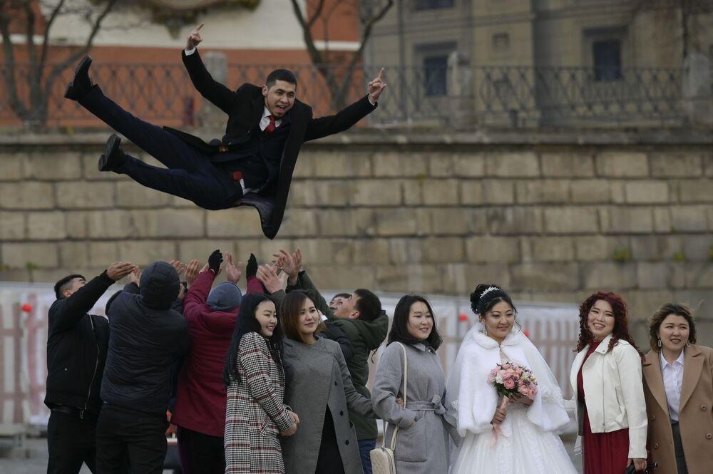 Novomanželé slaví svatbu a Rudém náměstí v Moskvě