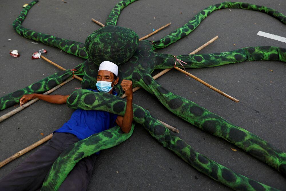 Rybář v ochranné masce leží na umělé chobotnici během protestu v Jakartě, Indonésie