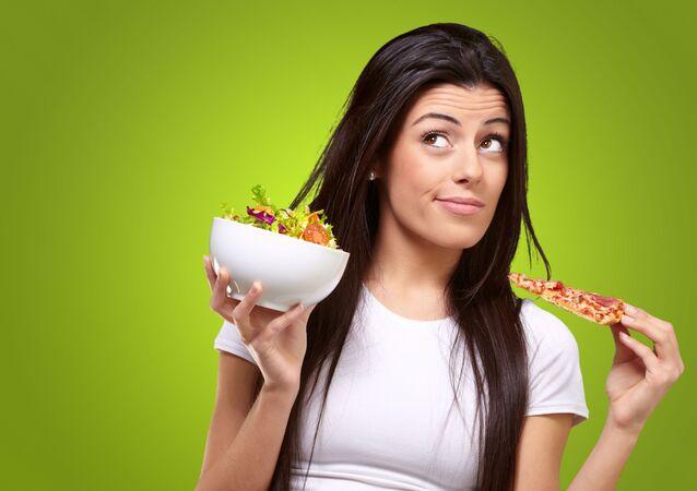 Dívka drží kousek pizzy a salát