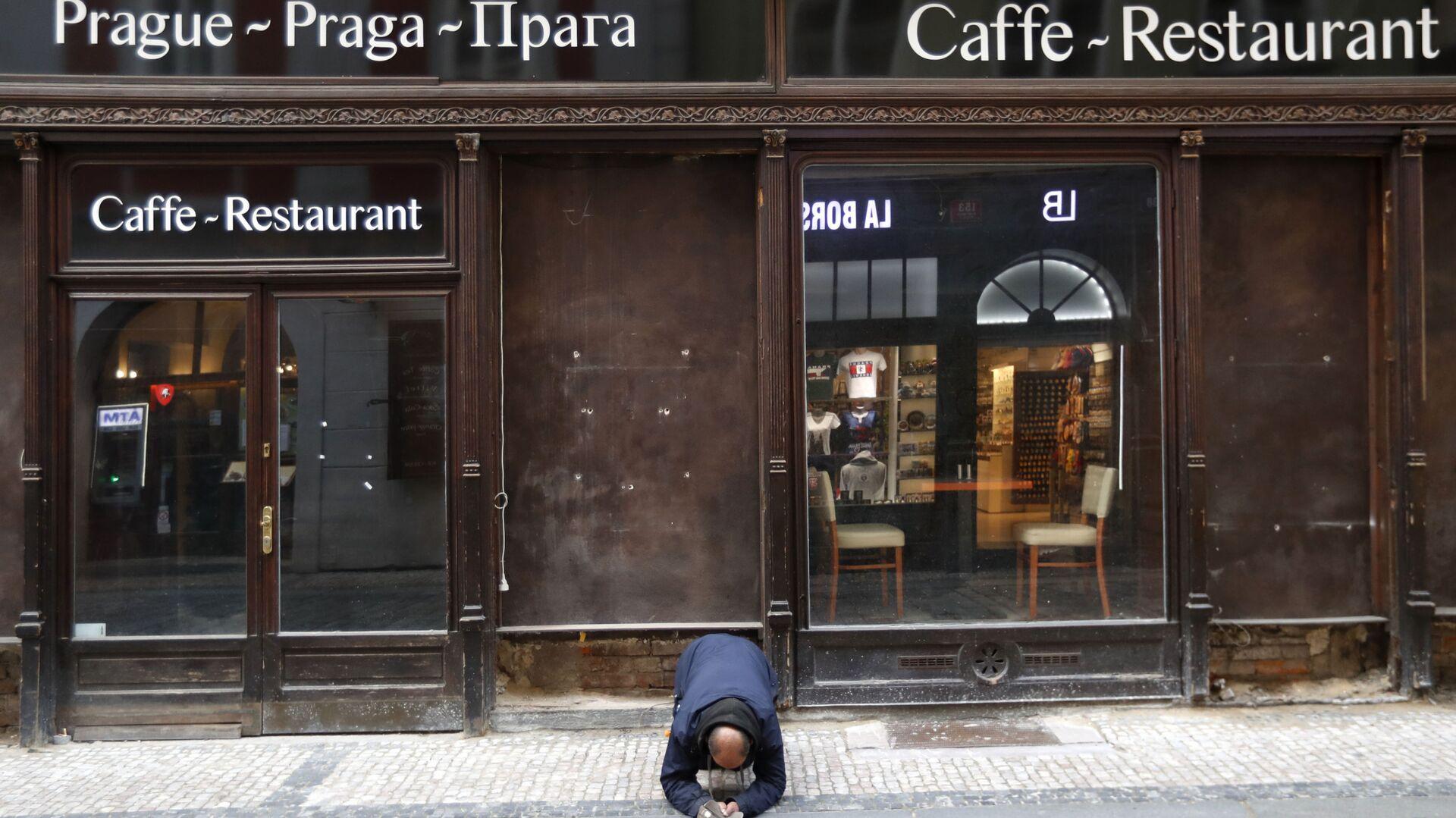 Muž žebrá před zavřenou restaurací v Praze - Sputnik Česká republika, 1920, 18.07.2021