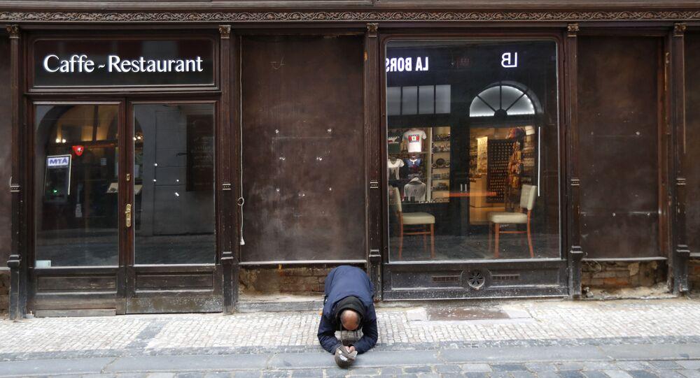 Muž žebrá před zavřenou restaurací v Praze