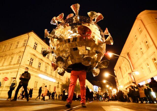 Muž v obleku covid-19 protestuje proti omezení kvůli koronaviru v Praze