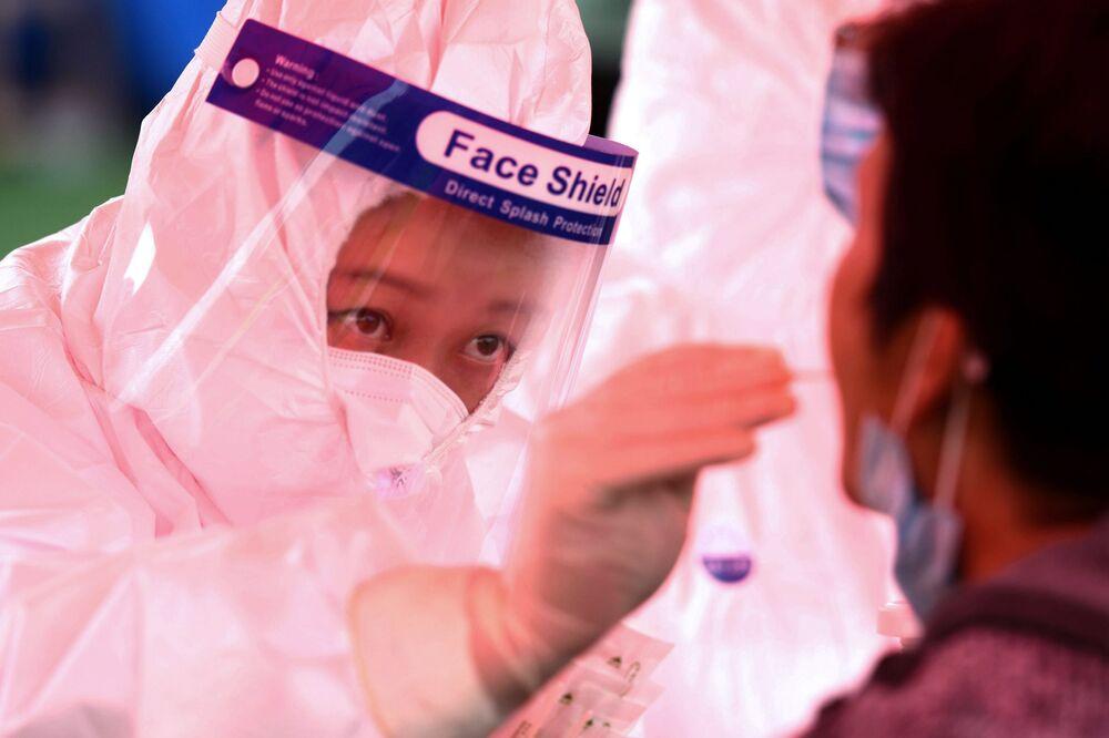 Zdravotnický pracovník odebírá vzorek místnímu obyvateli v rámci hromadného testování v Čching-tao, provincie Šan-tung.
