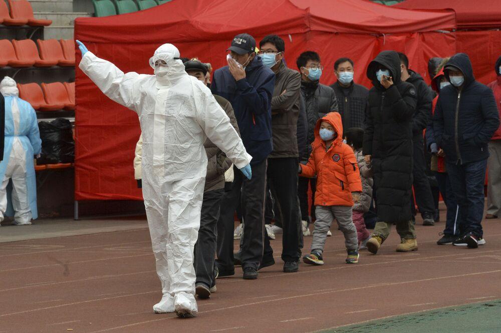 Pracovník v ochranném obleku vede lidi do dočasného testovacího centra ve městě Tchien-ťin.