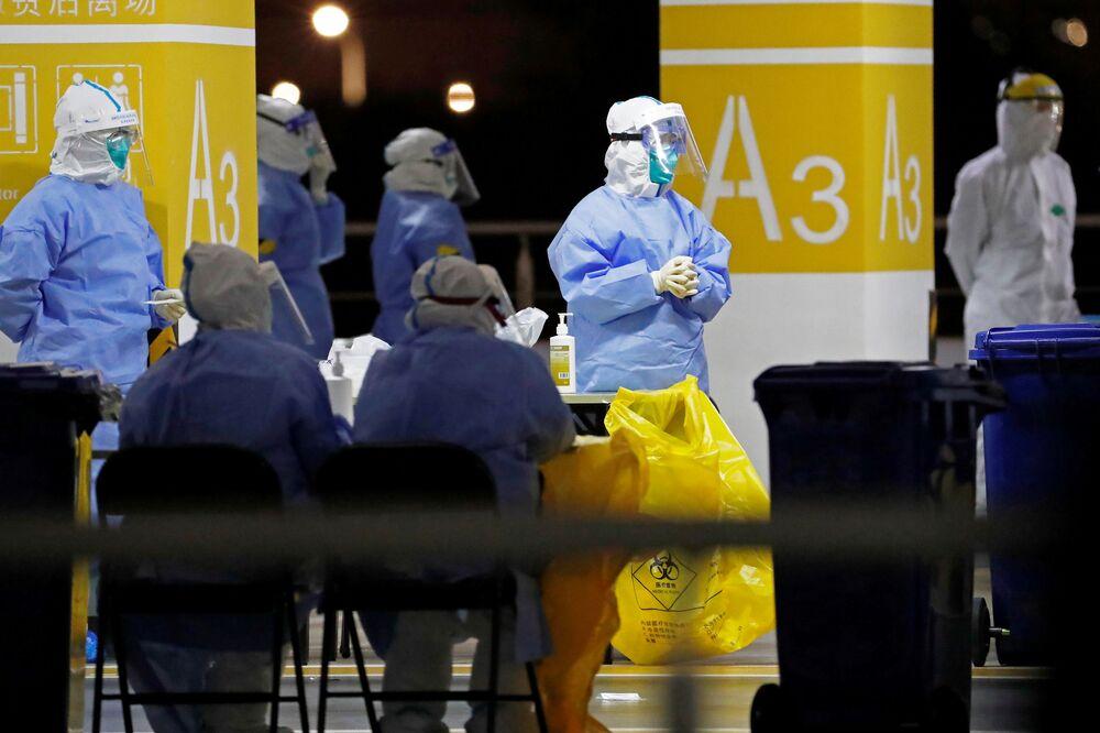 Lékaři v ochranných oblecích na odběrovém místě na mezinárodním letišti v Šanghaji.