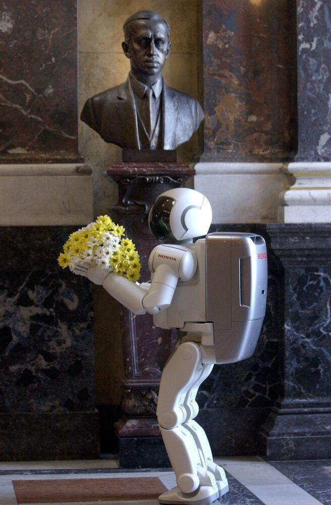 Humanoidní robot Asimo přináší květiny k bustě českého spisovatele Karla Čapka v sále Národního muzea v Praze, 2003.