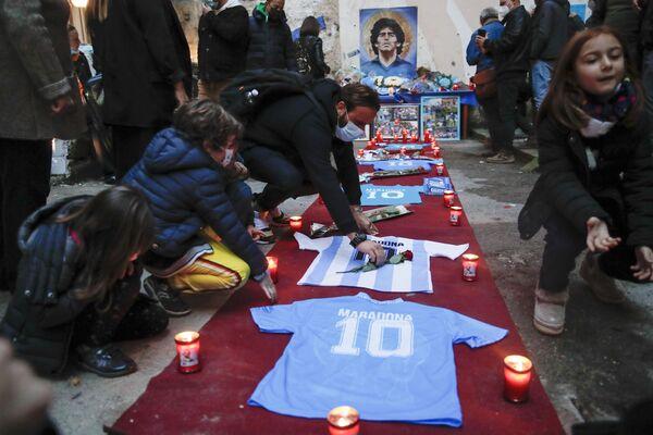 Lidé zapalují svíčky na počest fotbalové legendy Diega Maradony ve čtvrti Quartieri Spagnoli v Neapoli. - Sputnik Česká republika