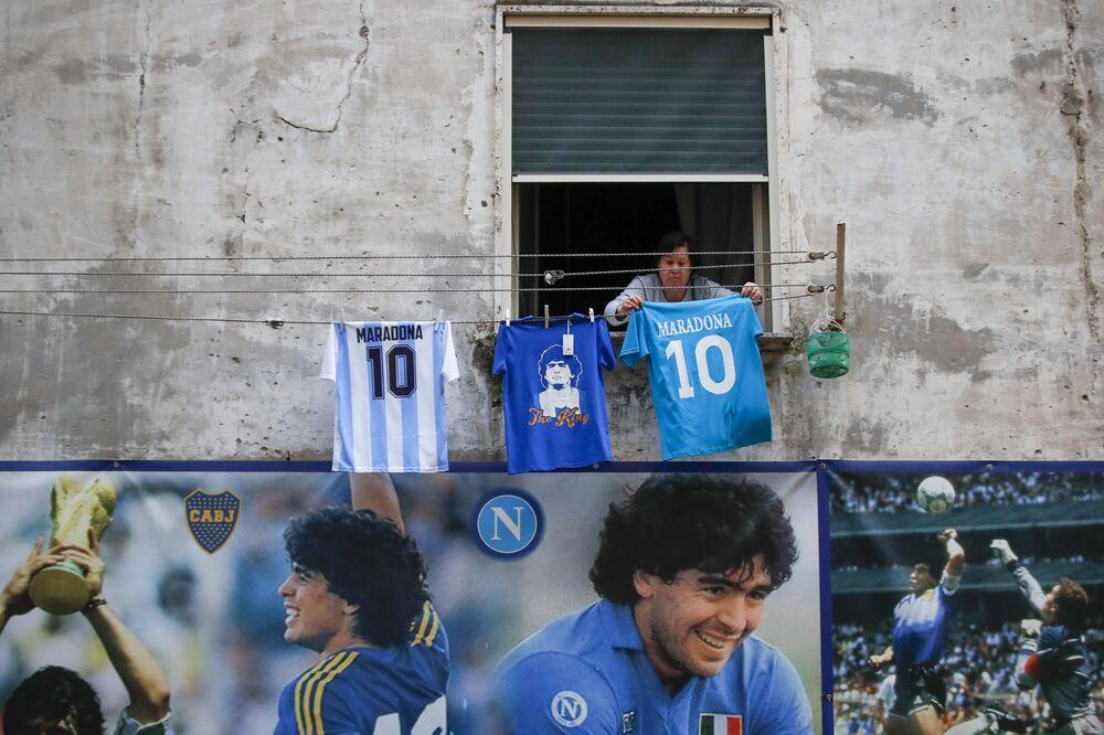 Žena věší dres s číslem 10 a nápisem Diego Maradonna v okrese Quartieri Spagnoli v Neapoli.