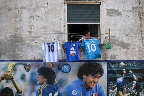Žena věší dres s číslem 10 a nápisem Diego Maradonna v okrese Quartieri Spagnoli v Neapoli. - Sputnik Česká republika