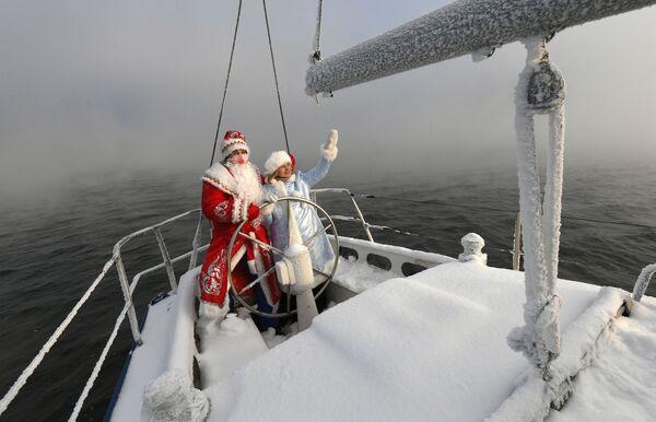 Členové jachtařského klubu Škiper v kostýmech Dědy Mráze a Sněhurky se loučí se starým rokem. - Sputnik Česká republika
