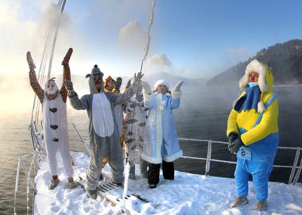 Členové jachtařského klubu Škiper si v karnevalových kostýmech hrají se sněhem během poslední letošní plavby na plachetnici. - Sputnik Česká republika
