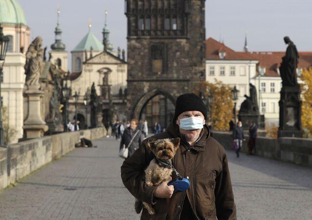 Muž v roušce na Karlově mostě v Praze