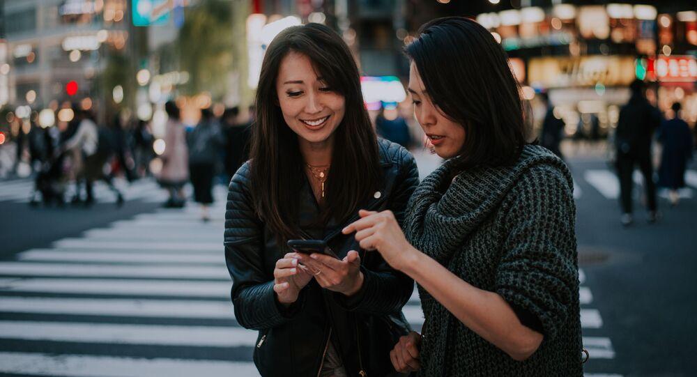 Dvě ženy na přechodu pro chodce v Tokiu, Japonsko