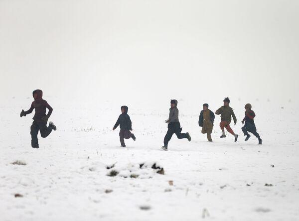 Afghánští chlapci si hrají během sněžení v Kábulu - Sputnik Česká republika